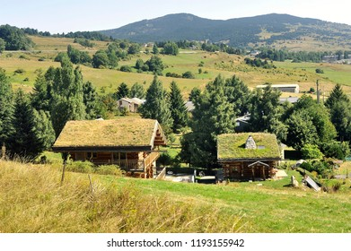 Wooden chalet with a roof with grass in a village in the Pyrenees seen from the little yellow train