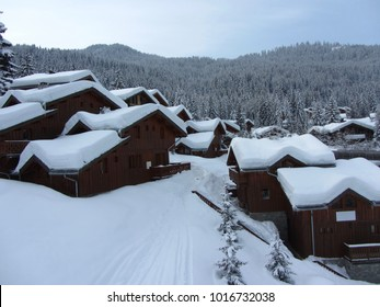 Wooden chalets of the ski resort La Tania Courchevel with lots of snow on the roofs