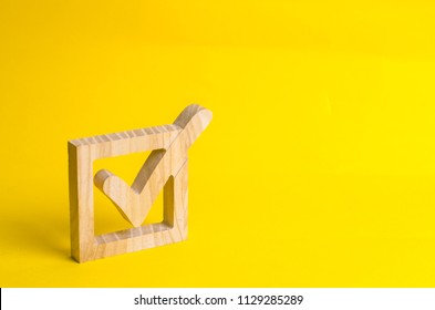 A wooden checkmark in the box on a yellow background. The concept of suffrage, voting in elections. Election of the President or Government. Democracy, development, civil initiative.