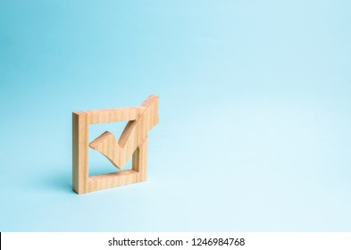 wooden checkmark for voting on elections on a blue background. Presidency or parliamentary elections, a referendum. Survey of the population, statistics, completed task. Democracy and freedom