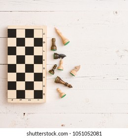 Wooden chess figures and chess board on white table background. Top view.