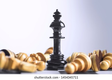 Wooden chess piece defeated by black king chess piece on the chessboard