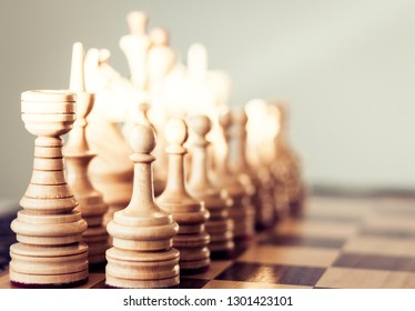Wooden chess pieces on a chessboard, leadership concept on white background