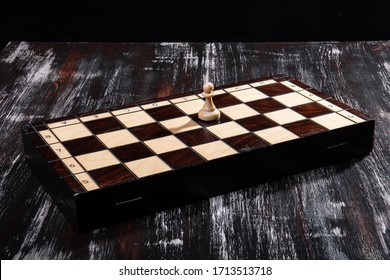 wooden chess pieces with a playing board against a dark background