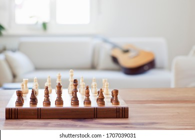 Wooden chessboard on a table in a bright living room with couch and guitar in the background - focus on the chessboard