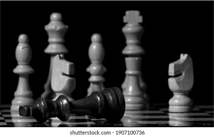Wooden chessboard and pieces. Checkmate. On black background