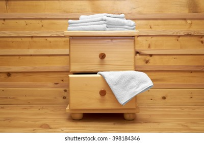 wooden chest of drawers with bath towel