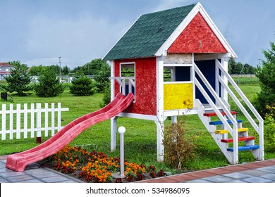 wooden children playhouse with slides in backyard spring garden
