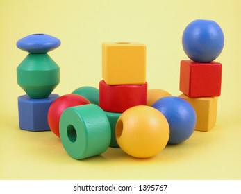 wooden childrens blocks of different colors - yellow background