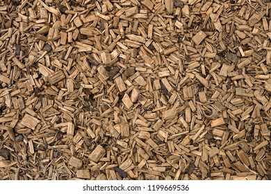 Wooden chips texture. Overhead shot. Brown chipped wooden pieces used as decoration. Kids Playground Mulch. Woodchips, wood, that has been chipped. Pieces of wood formed by cutting or chipping