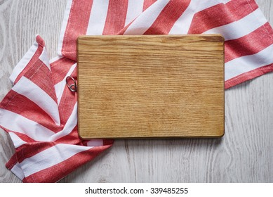 Wooden chopping board on brushed white table with striped kitchen towel top view