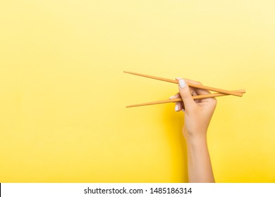 Wooden chopsticks holded with female hands on yellow background. Ready for eating concepts with empty space.