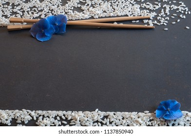 wooden chopsticks on black plain with grains of white rice