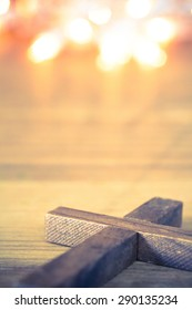 A wooden Christian cross laying on softly lit background. Room for copy.