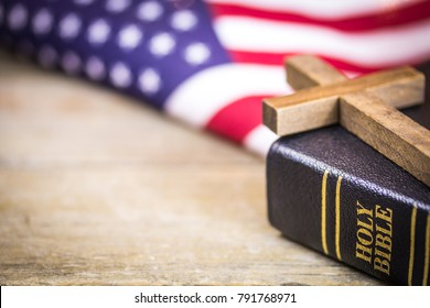 A wooden Christian cross laying on a holy Bible with an American flag background.