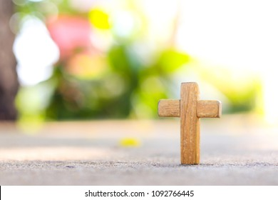 Wooden Christian cross on concrete floor with blurred nature background. Wooden Christian cross background. Christianity Concept. Faith hope love concept.