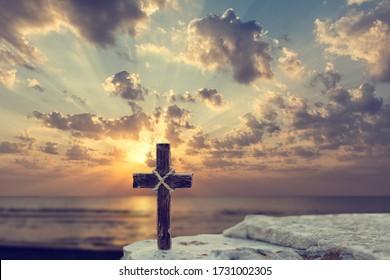 Wooden Christian cross on rocks against beautiful golden sunrise above the sea