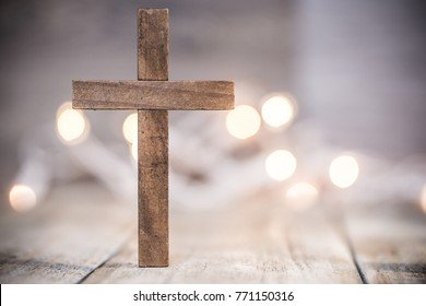A wooden Christian cross on a soft bokeh light and wood background.