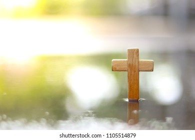 Wooden Christian cross is standing in the water. Wooden Christian cross background. Christianity Concept. Faith hope love concept.