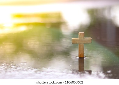 Wooden christian cross is standing in the water. Christianity symbol. Faith hope love concept.