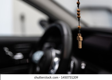 Wooden Christian rosary with crucifix hanging on car rear mirror.