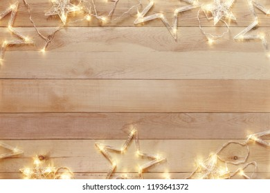 Wooden christmas background with bright garland. Copy space.