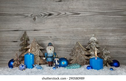 Wooden christmas background in grey with blue turquoise nutcrackers, snow and candles in country style decoration.