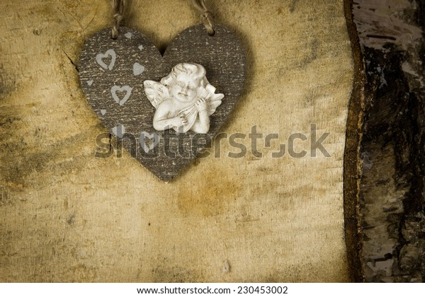 wooden Christmas heart with angel inside and heart  on the wooden birch background