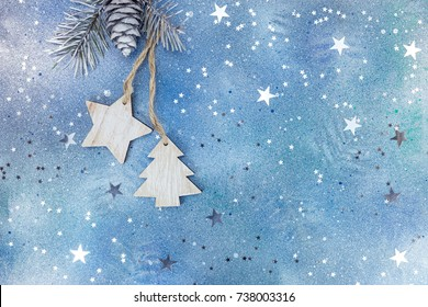 wooden christmas holiday decorations on silver-blue background with star confetti