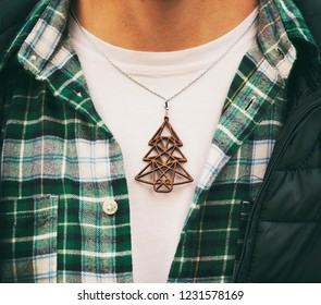 The wooden christmas necklace with shape of fir on the man's neck in a green shirt