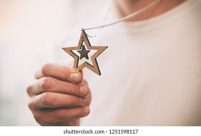 The wooden christmas necklace with shape of star in the man's hand