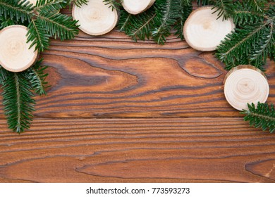 Wooden Christmas or New Year background with a top border made of natural fir tree branches and wooden slices on a rustic wooden table. Space for your text or image.Top view.