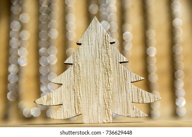 Wooden Christmas tree on wooden table, reflections on background, Christmas chains
