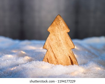 Wooden Christmas tree in a snowy landscape in front of a dark background