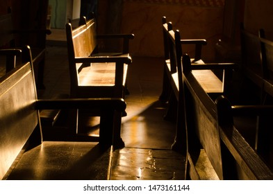 Wooden church pews in dramatic light