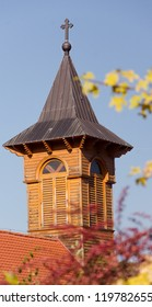 A wooden church tower between autumn tree branches, beautiful autumn scene