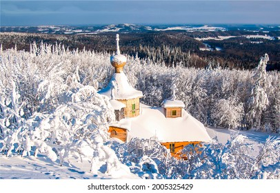 Wooden church in the winter snow forest. Church in snowy forest in winter. Wooden church in winter snow forest