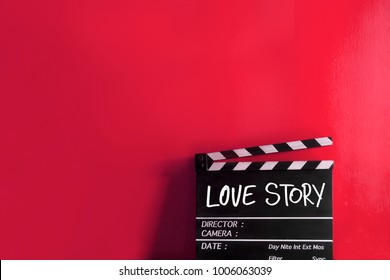 Wooden clapper board on red background and Title Love story