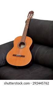 Wooden classical guitar on the grey sofa