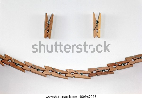 Wooden clip on white background with smiling shape
