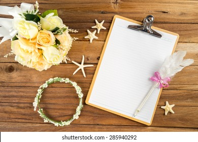 Wooden Clipboard attach planning paper with pen on top beside rose headband, tiara, bouquet, starfish