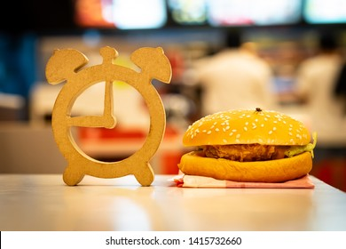 Wooden clock model and hamburger put on the white table with housefly. Fast food restaurant with blur customer, Rush-hour in city life, fast food, people and unhealthy eating concept.