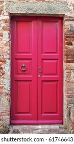 Wooden closed pink door with brick wall around it.