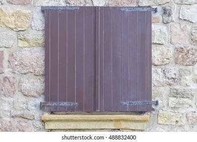Wooden closed window on a stone wall