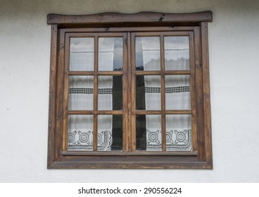 Wooden closed window with white lace curtains,