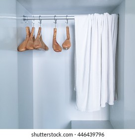 wooden clothes hanger and towel on clothes rail. White Hotel hanger in the wardrobe.  selective focus. filter effect.