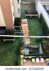 A wooden clothespin attached to a rope overlooking the vacuum. Suspended clothspin, vertigo over a balcon on the 3th flor