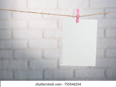 Wooden clothespin and blank paper on a rope against white brick wall,TODAY letters