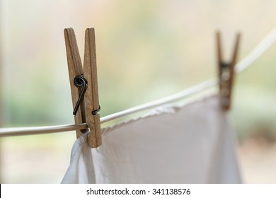 Wooden clothespins holding a white shirt on an outdoor laundry line.