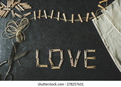 Wooden clothespins on a black background ( Love )